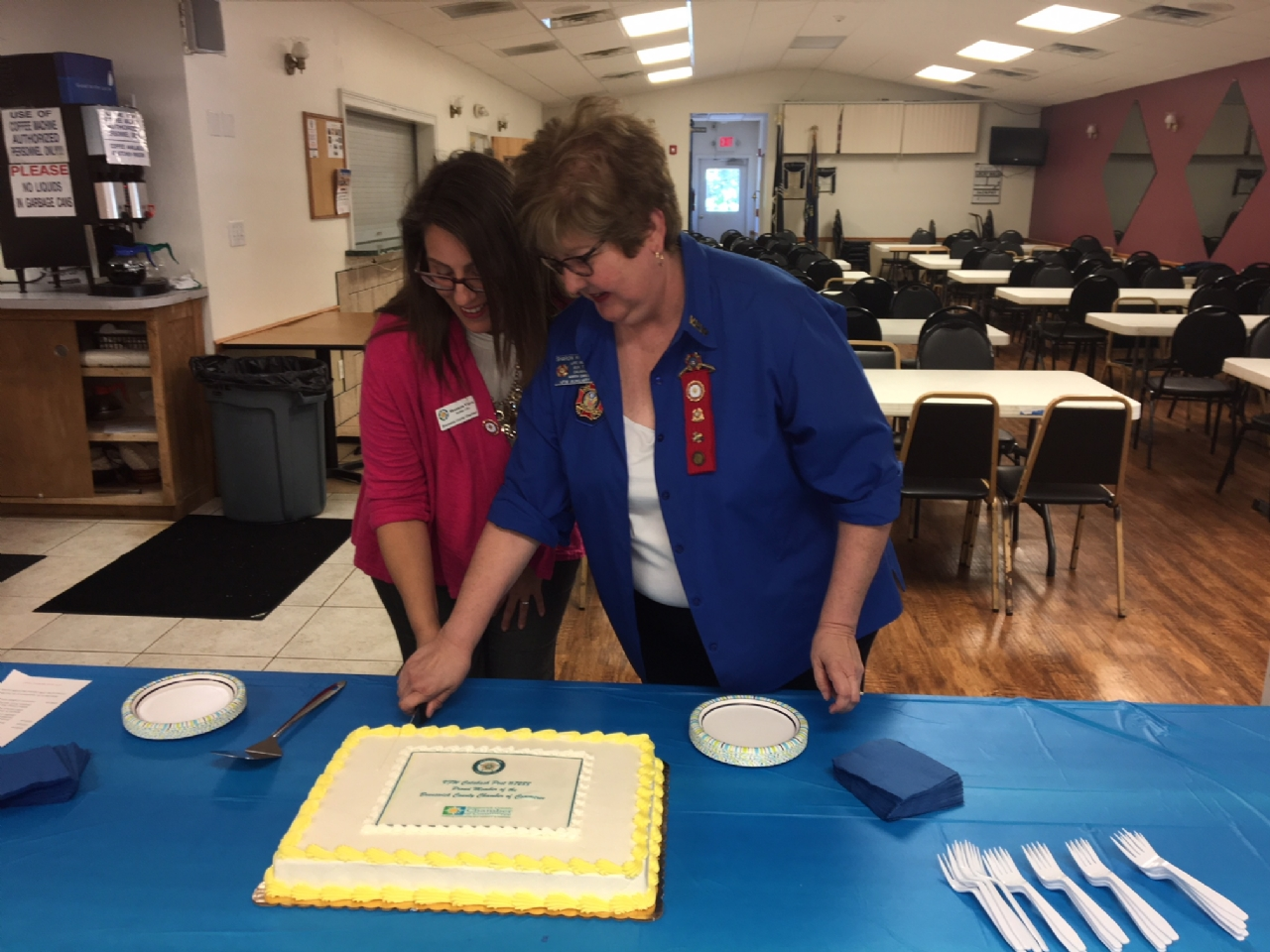 Shannon Viera, President/CEO, Brunswick County Chamber of Commerce on the left and Sharon Kossler, President, VFW Calabash Post #7288 Auxiliary cut the cake following the ribbon cutting ceremony.