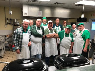 The St. Patrick's Day kitchen crew had the task of preparing and serving the feast of corned beef, cabbage, potatoes, and jumbo carrots along with green - mint chocolate chip ice cream and Irish Coffee.  From left to right are: Joe Nance, Dave Gibbons; Chaz Rowe, Wayne Spears, Bill Gajewski, Jim Bicknell, Jim Stueve, Bob Stocklin and Tommy Lynn all dressed for the day.
