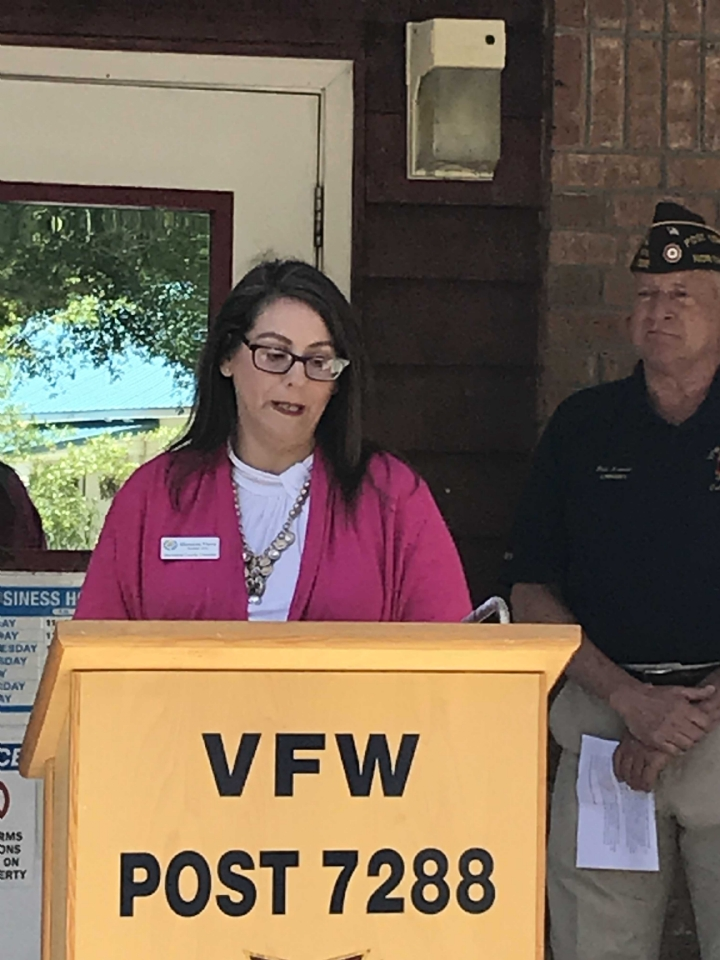 Brunswick County Chamber of Commerce President, Shannon Viera, provides opening remarks to the ribbon cutting ceremony as VFW Commander, Rick Arvonio, looks on.