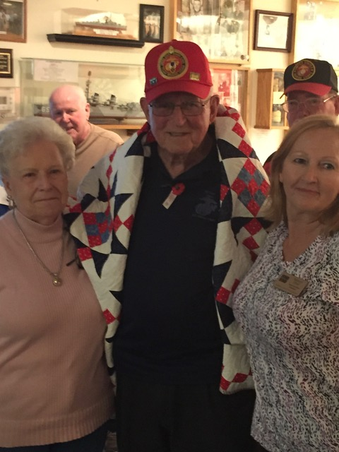 Retired USMC Rich Murray receives a Quilt of Valor from Cathy Elliott and Julia Larson.